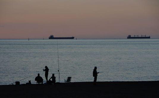 Gente pescando en la playa de Ereaga